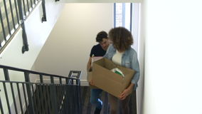 Couple Moving Into New Home Carrying Box Upstairs. Couple carrying boxes up stairs as they move into new home.Shot on Sony FS700 in PAL format at a frame rate of stock video footage