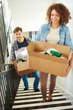 Couple Moving Into New Home Carrying Box Upstairs. With Items In Smiling Stock Image
