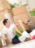 Couple moving into new home. With door keys and boxes Royalty Free Stock Image