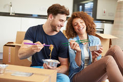 Couple Moving Into New Home Enjoying Takeaway Meal Royalty Free Stock Photos