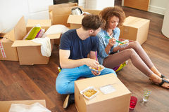 Couple Moving Into New Home Enjoying Takeaway Meal. High View Of Couple Moving Into New Home Enjoying Takeaway Meal Royalty Free Stock Image