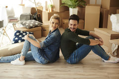 Couple moving new home. Side view of couple sitting back to back Stock Photo