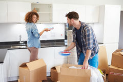 Couple Moving Into New Home And Unpacking Boxes. In Kitchen Looking At Each Other Royalty Free Stock Images