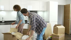 Couple Moving Into New Home And Unpacking Boxes. Couple unpacking boxes in new home and putting things away. Shot on Sony FS700 in PAL format at a frame rate of stock footage