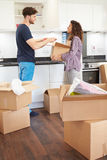 Couple Moving Into New Home And Unpacking Boxes Stock Images
