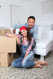 Couple moving in new house. Couple sitting in new house with boxes royalty free stock photos