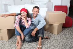 Couple moving in new house. Couple sitting in new house with boxes royalty free stock image