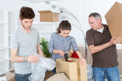 Couple moving in new house and closing carton boxes Royalty Free Stock Photography