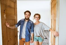 Couple moving in new house, entering through the door. Stock Photo