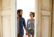 Couple moving in new house, entering through the door. Royalty Free Stock Photography