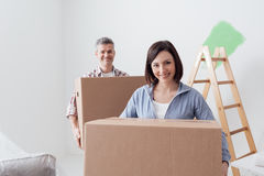 Couple moving into a new house. Happy couple moving into a new house and doing home renovations, they are carrying cardboard boxes stock photo