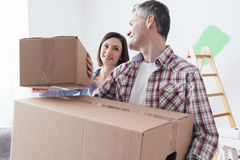 Couple moving into a new house. Happy couple moving into a new house and doing home renovations, they are carrying cardboard boxes Stock Photos