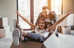 Couple moving in new house. Happy couple is having fun with cardboard boxes in new house at moving day stock photo