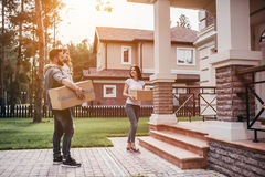 Couple moving in new house. Happy couple is standing near new house with cardboard boxes. Moving day royalty free stock photography