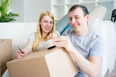 Couple moving into new house. Happy young couple moving into new house stock image