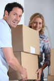 Couple moving pile of boxes. Couple moving a pile of large cardboard boxes Royalty Free Stock Image