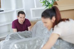 Couple moving sofa taking after moving houses stock photos