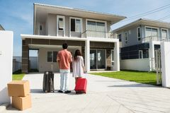 Couple moving to new house. Husband and wife standing in front of new buying home with luggage and  boxes. Happy Asian married male and female couple move to Royalty Free Stock Images