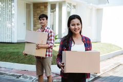 Couple moving to their new house holding cardboard box stock photography