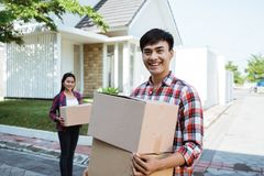 Couple moving to their new house holding cardboard box royalty free stock photography