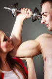 Couple muscular man and girl admiring his strength. Stock Image