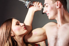 Couple muscular man and girl admiring his strength. Royalty Free Stock Photos