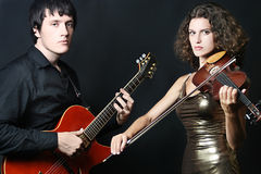 Couple of musicians. People of entertainment and performance. Portrait of musical couple, man guitarist and woman violinist on black Royalty Free Stock Photography