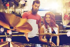 Couple of musicians with drum kit at music store. Sale, people, musical instruments and entertainment concept - happy couple of musicians with drum kit at music Royalty Free Stock Photo