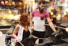 Couple of musicians with drum kit at music store. Sale, people, musical instruments and entertainment concept - happy couple of musicians with drum kit at music Royalty Free Stock Photography