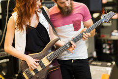Couple of musicians with guitar at music store Stock Photo
