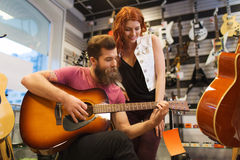 Couple of musicians with guitar at music store Royalty Free Stock Images