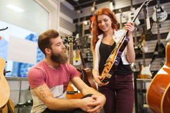 Couple of musicians with guitar at music store Stock Photos