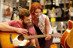 Couple of musicians with guitar at music store Stock Images
