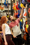 Couple of musicians with guitar at music store Royalty Free Stock Image