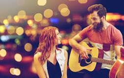 Couple of musicians playing guitar over lights Stock Photography