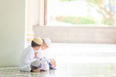 Couple Muslim boy in traditional clothing reading Koran in the m stock images