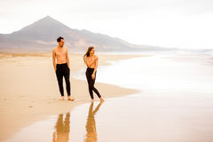 Couple with naked torso on the beach. Young couple with naked torso enjoying beautiful sandy beach with mountains on background on Fuerteventura island in Spain Stock Photo