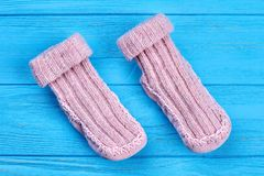 Couple of natural wool knitted socks. Close up handmade warm socks for girls on blue wooden background. Pair of soft knitted socks for kids Royalty Free Stock Photo