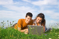 Couple is nature. Young couple studying on the grass with a laptop Royalty Free Stock Photos