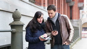 Couple navigating with city map and smartphone Royalty Free Stock Images