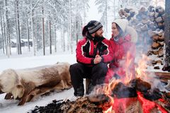 Couple near bonfire in winter landscape royalty free stock photo
