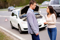 Couple near broken car on a highway roadside.  Royalty Free Stock Photography