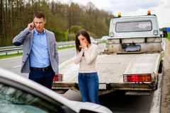 Couple near broken car on a roadside.  Royalty Free Stock Image