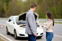 Couple near broken car on a roadside Stock Photos