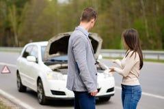 Couple near broken car on a roadside Stock Photos