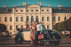 Couple near classic car. Wealthy couple near classic convertible against royal palace Royalty Free Stock Photography