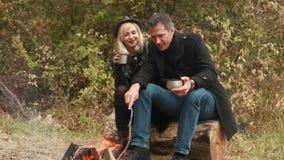 Couple near fire drinking coffee or tea. Couple in love sitting near fire and drinking coffee or tea stock video footage