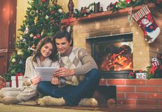 Couple near fireplace in Christmas decorated house.  Stock Photo