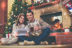 Couple near fireplace in Christmas decorated house.  Stock Photos