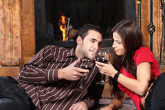 Couple near fireplace holding glass of wine Stock Image